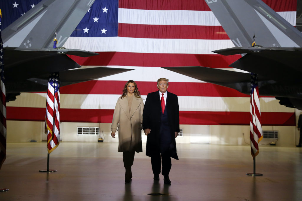 President Trump and First Lady Melania Trump walk by fighter jets in front of a big American flag