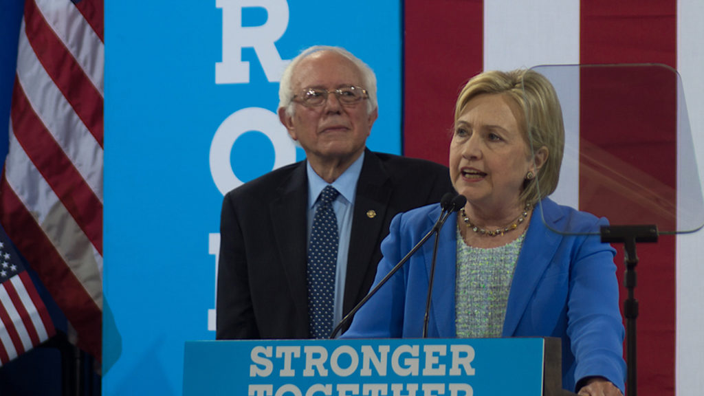 Hillary Clinton speaking at a podium with Bernie Sanders standing behind