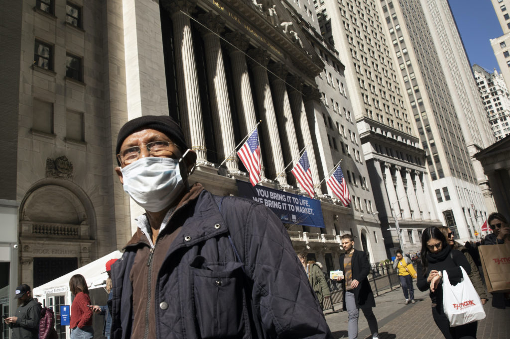 Man wearing mask in front of New York Stock Exchange building